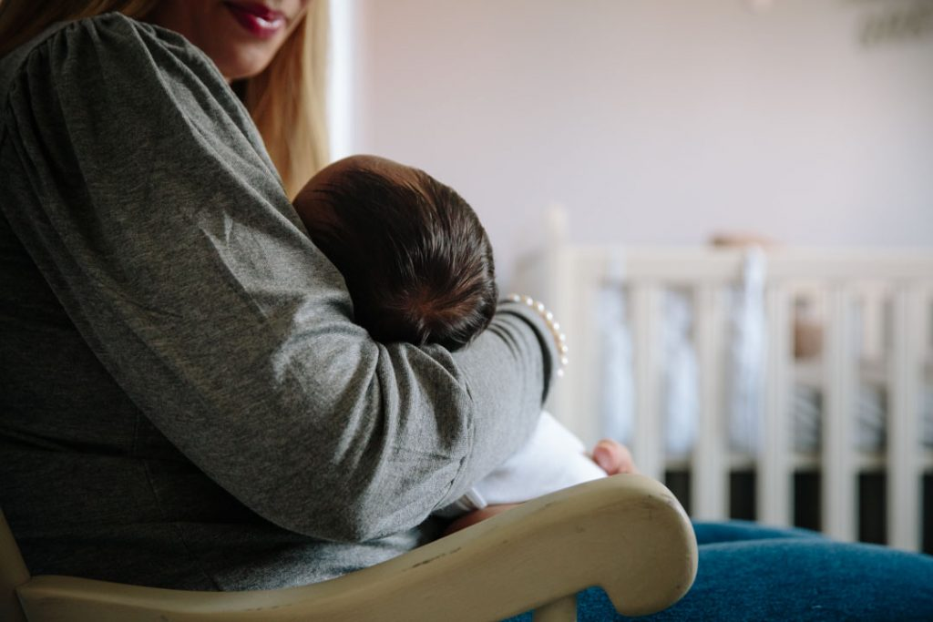 newborn baby being cuddled close by Mum