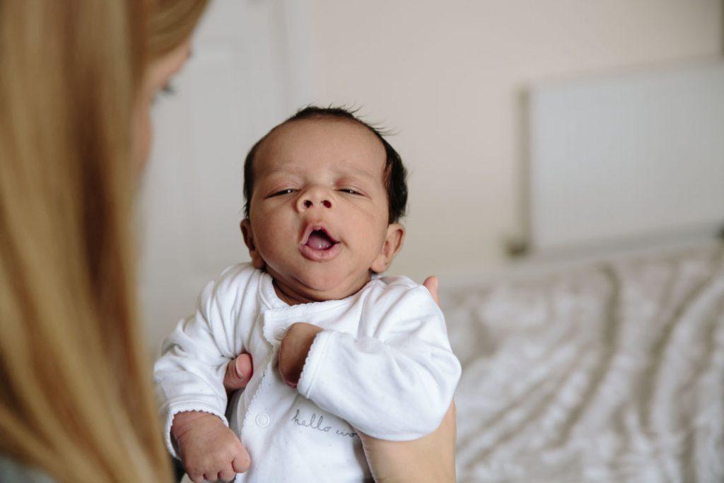 Newborn baby being held by Mum