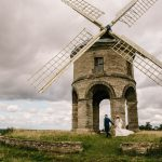 Bride and groom walking in front of Chesterton Windmill in Leamington