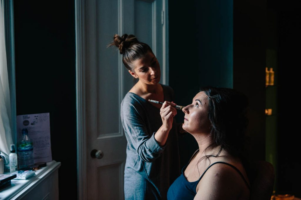 Bride having her makeup done in the window light at Hampton Manor