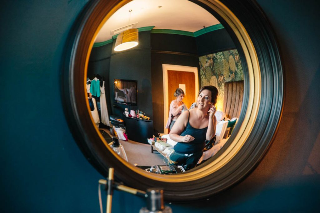 Bride looking in a circular mirror to put her earrings in