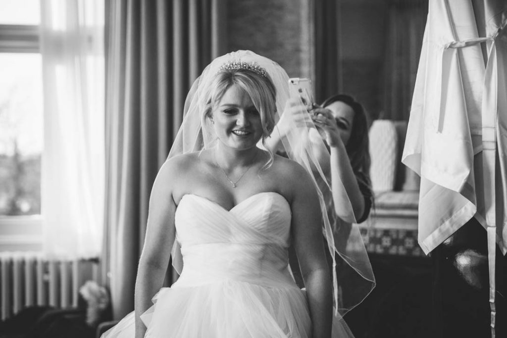 Hairdresser taking a photo of the Bride's hair and veil