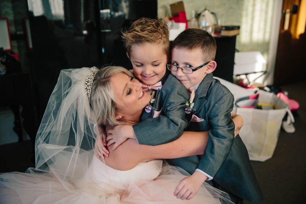 Bride hugging her 2 page boys