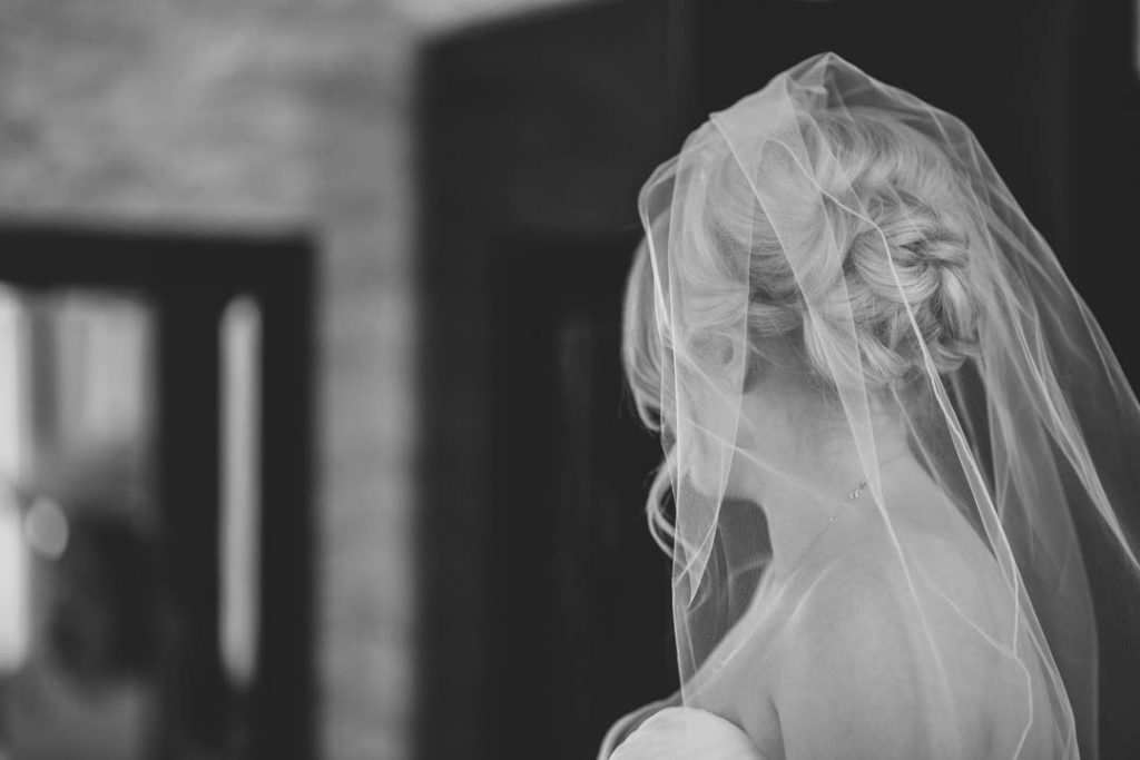 Black & white image of bridal hair covered in her veil as she looks away from the camera