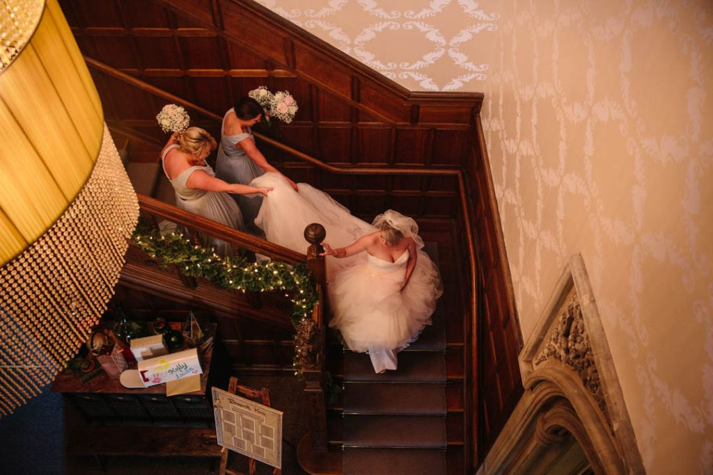 Bride walking down the stairs with her Bridesmaids holding her dress at Hampton Manor