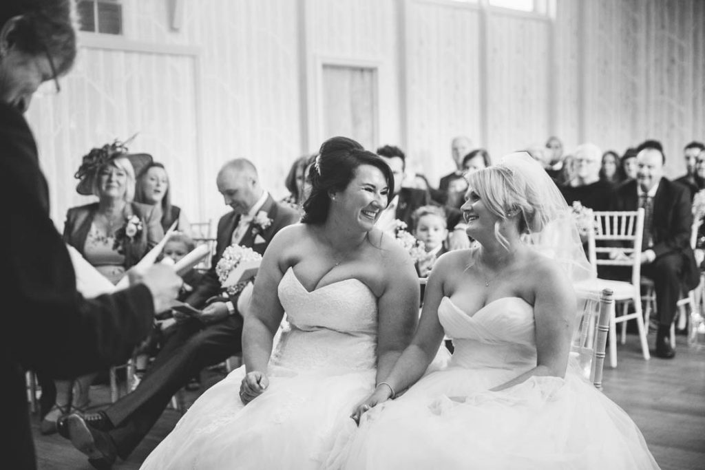 Two brides laughing during their wedding ceremony at Hampton Manor