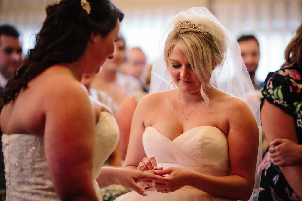 Two brides, exchanging wedding rings, Hampton Manor