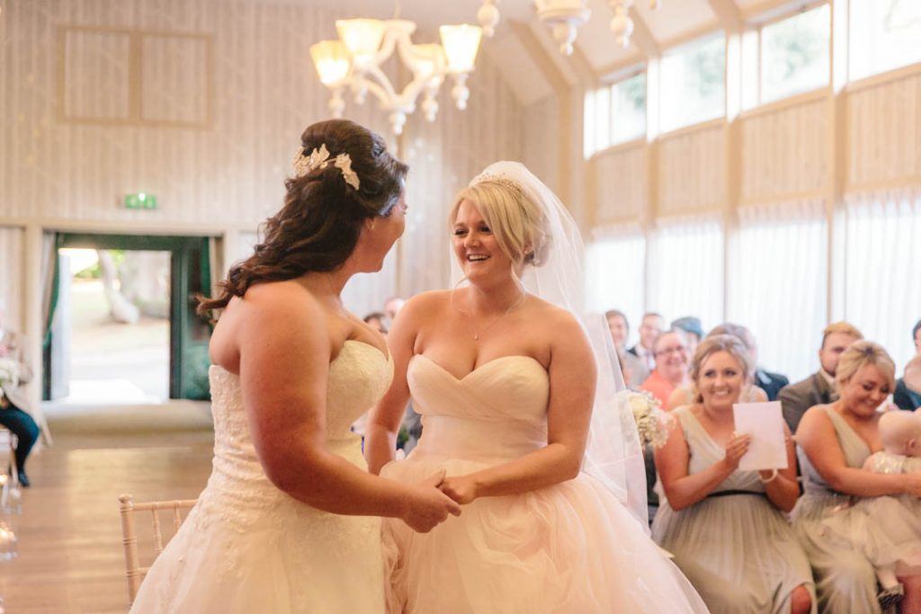 Two brides during their wedding ceremony at Hampton Manor