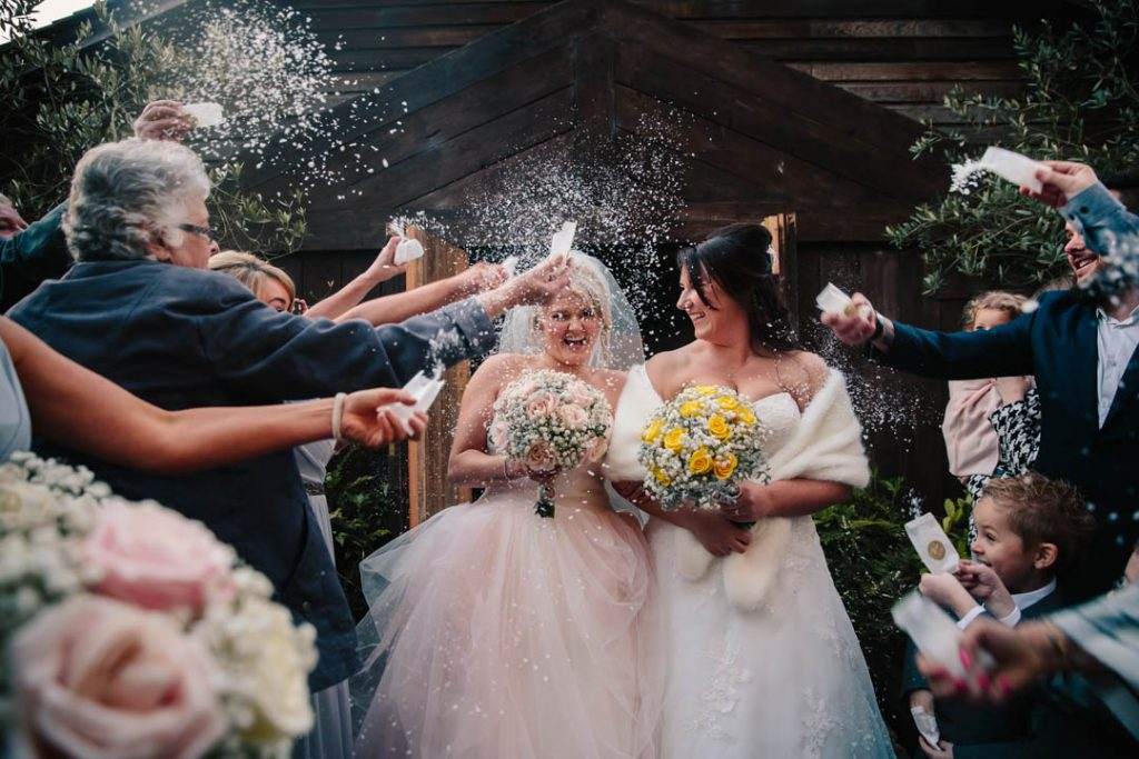 Guests throwing snowfetti over two brides after their wedding at Hampton Manor