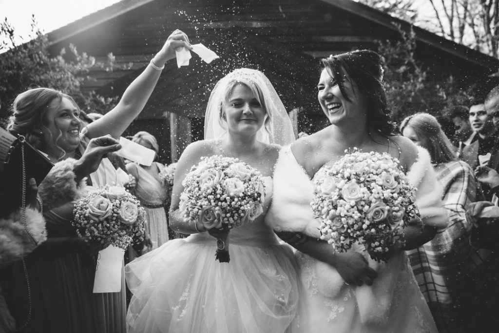 black & white image of guests throwing snowfetti over two brides, just married at Hampton Manor