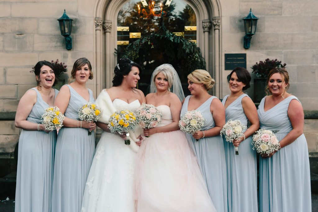 Two Brides laughing with their bridesmaids