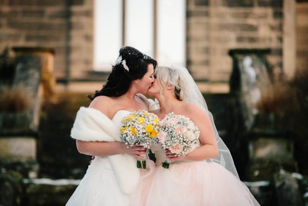 Bride & Bride kissing. winter wedding at Hampton Manor