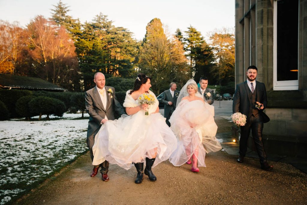 Two BRides walking outside Hampton Manor in their wellies