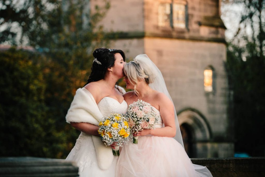 Bride kissing Bride's forehead, standing together with their wedding bouquets