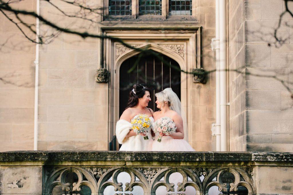 Bride and Bride standing together outside door of Hampton Manor