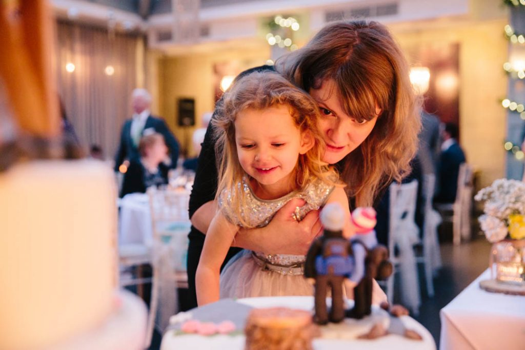 Little girl and her Mum looking at the wedding cake, Hampton Manor