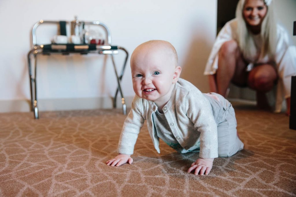 Baby crawling and grinning, bridal prep