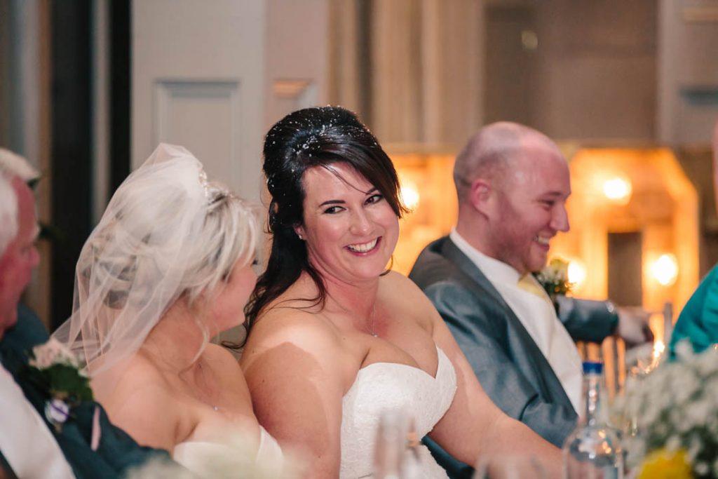 Bride smiling at Bride during speeches at Hampton Manor
