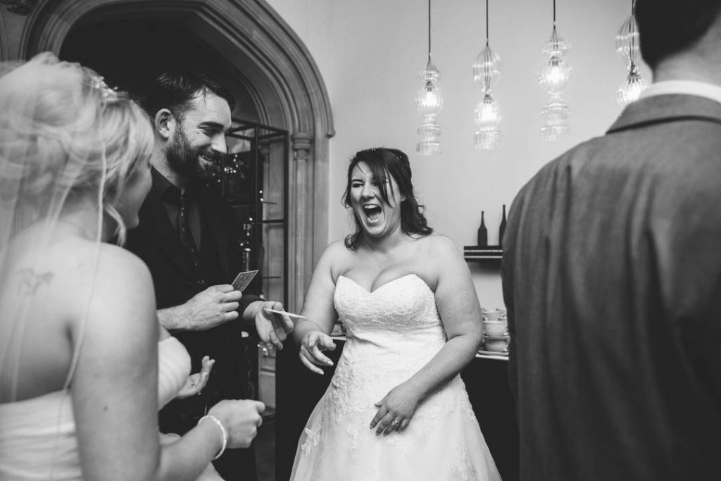 Bride laughing at the Magician's trick- wedding at Hampton Manor
