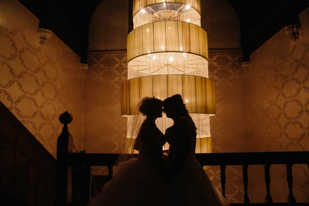 silhouette of two brides in front of the chandelier at Hampton Manor