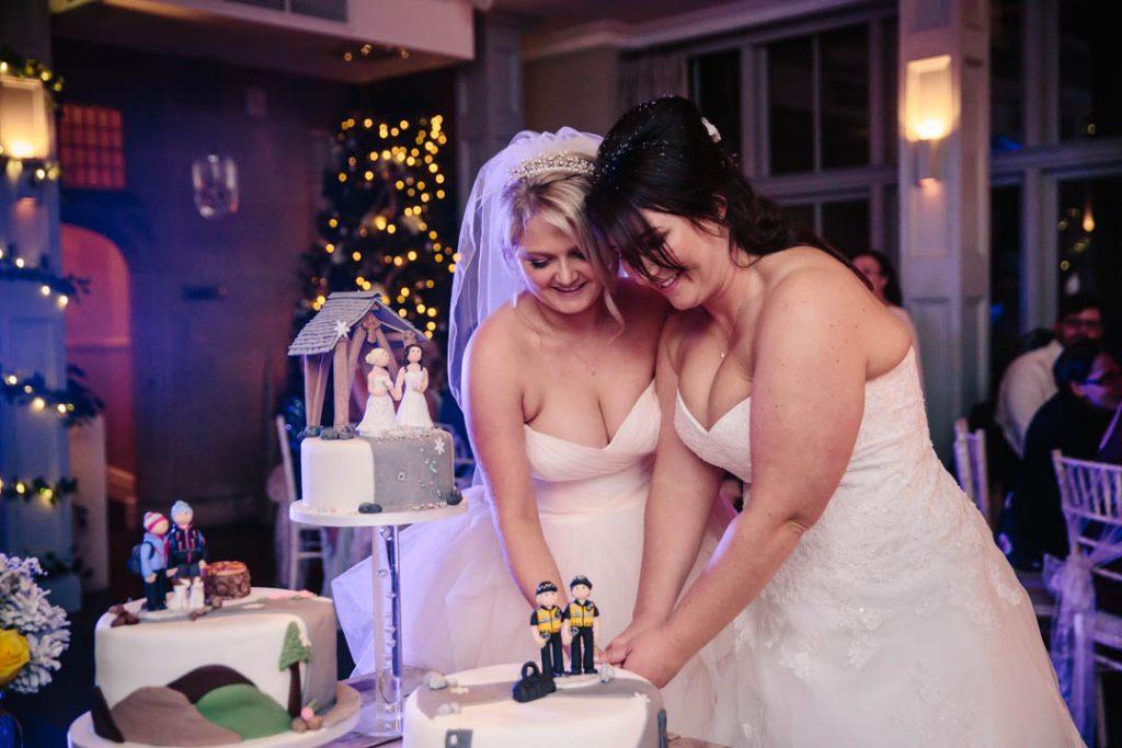 Two brides cutting their wedding cake at Hampton Manor