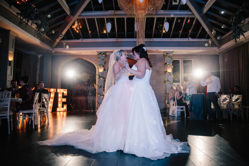 Two brides dancing their first dance at their wedding at Hampton Manor