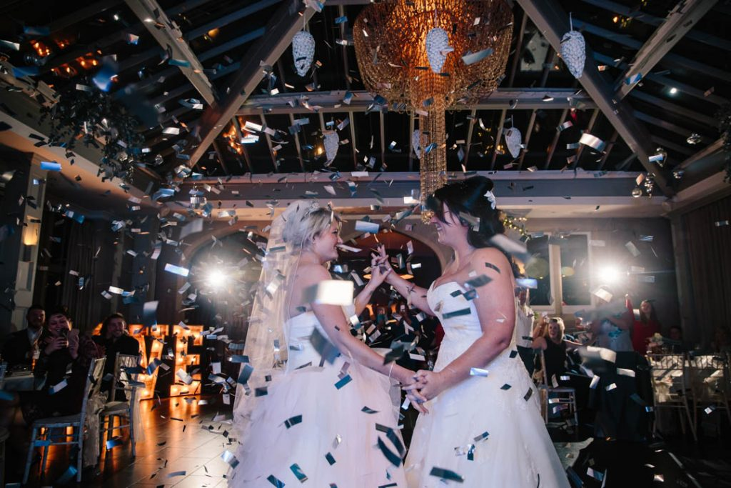 Two brides dancing their first dance, confetti canon, Hampton Manor wedding