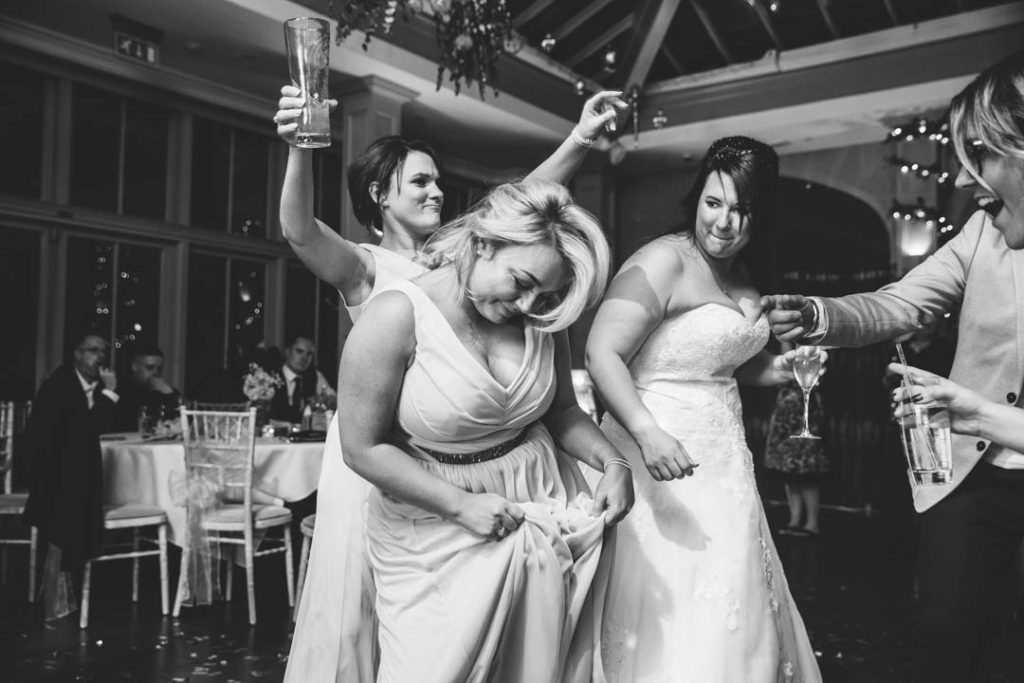 Bride and bridesmaid dancing at a wedding at Hampton Manor