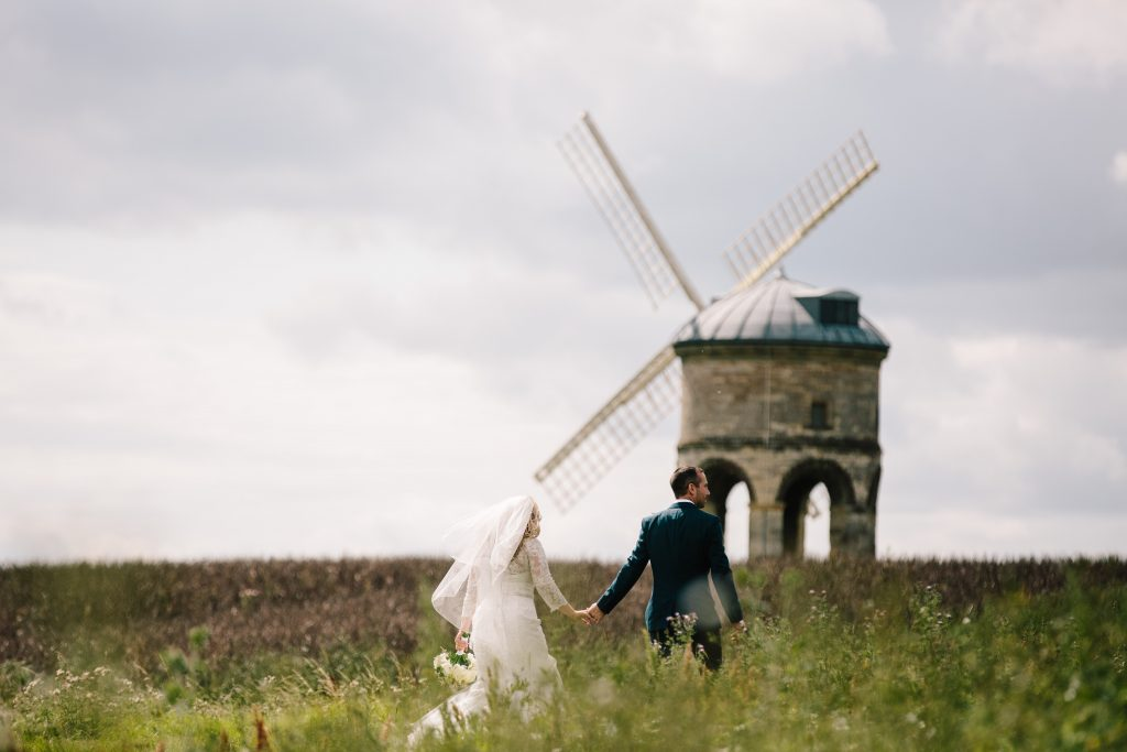 Bride and Groom holding hands, walking towards windmill