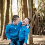 Two brothers laughing together in the woods