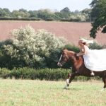Bride galloping a horse in a wedding dress