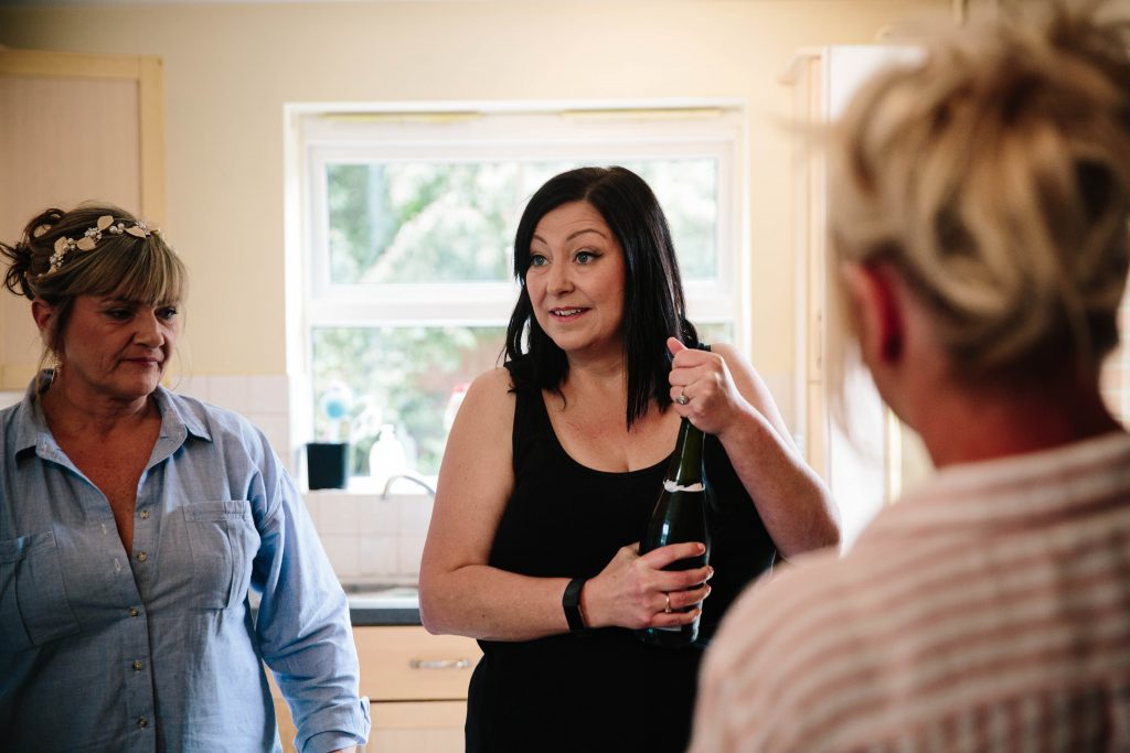 Bride opening prosecco on wedding morning