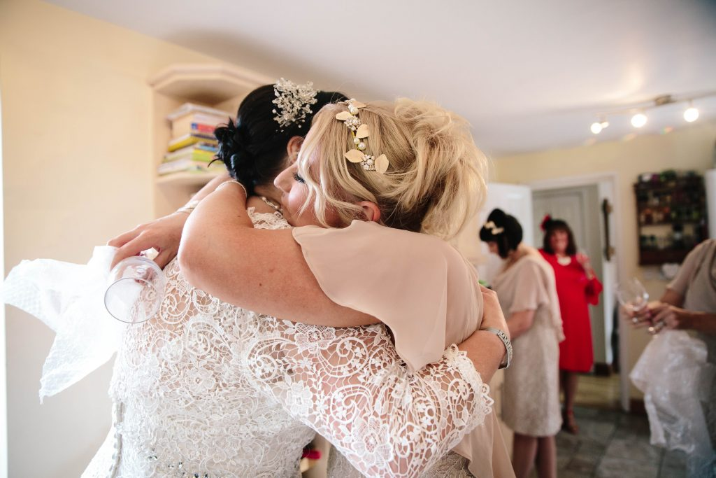 bridesmaid hugging bride after opening a gift