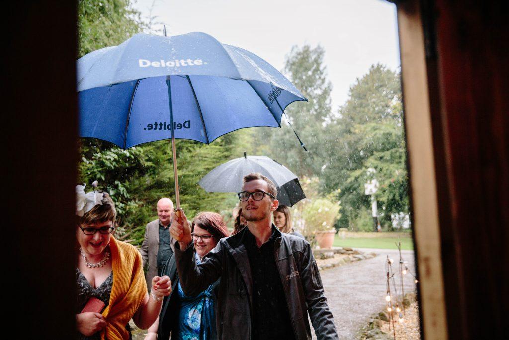 guests walking into wedding ceremony under umbrellas in the rain