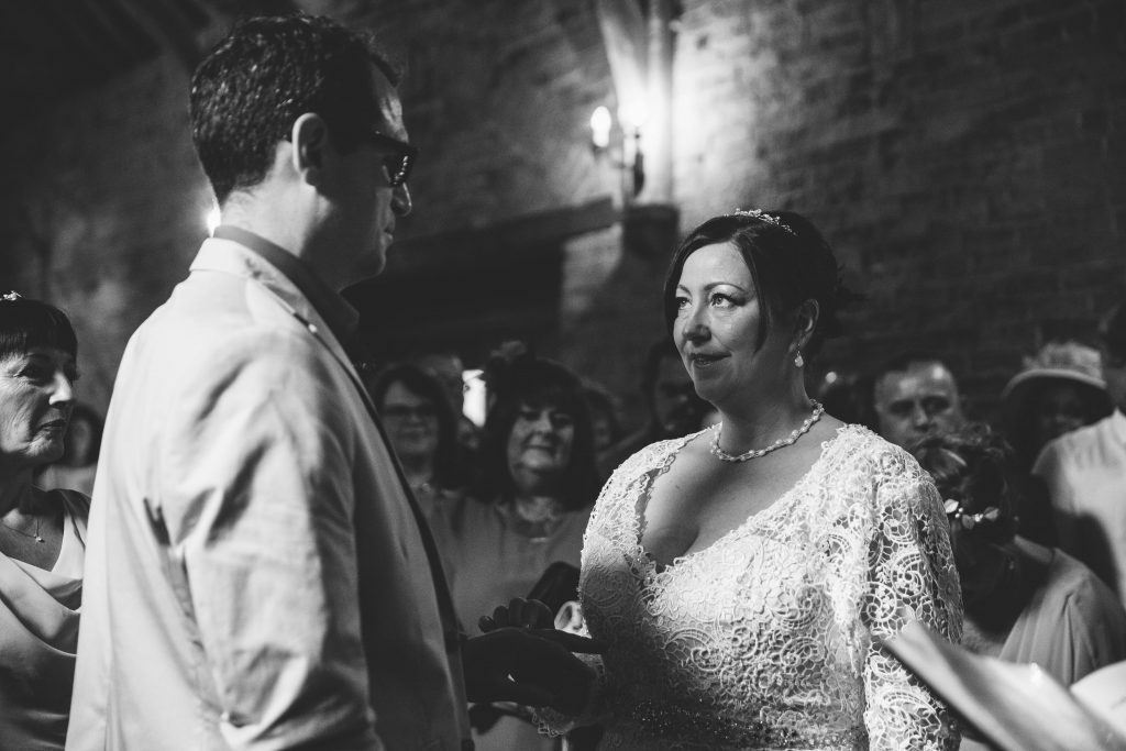 Bride & Groom, exchanging wedding rings during wedding ceremony at Dovecote Barn