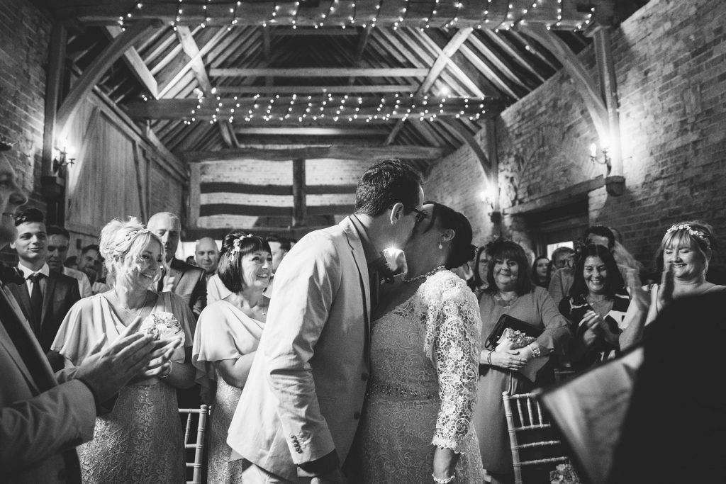 Bride & Groom first married kiss during wedding ceremony at Dovecote Barn