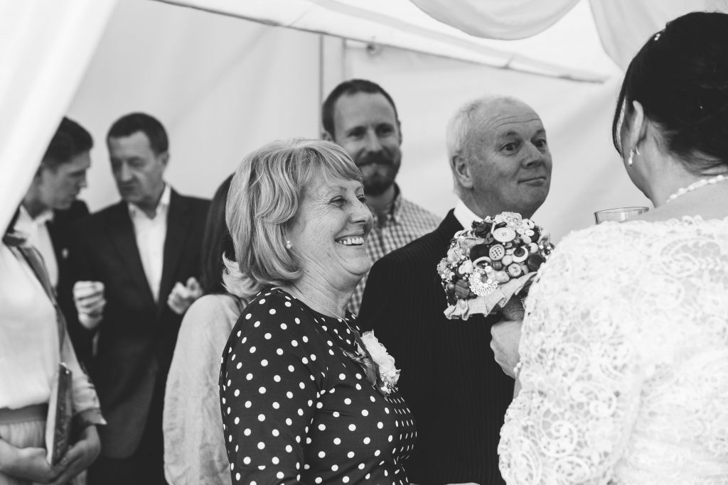 Bride greeting guests after wedding ceremony at Dovecote Barn
