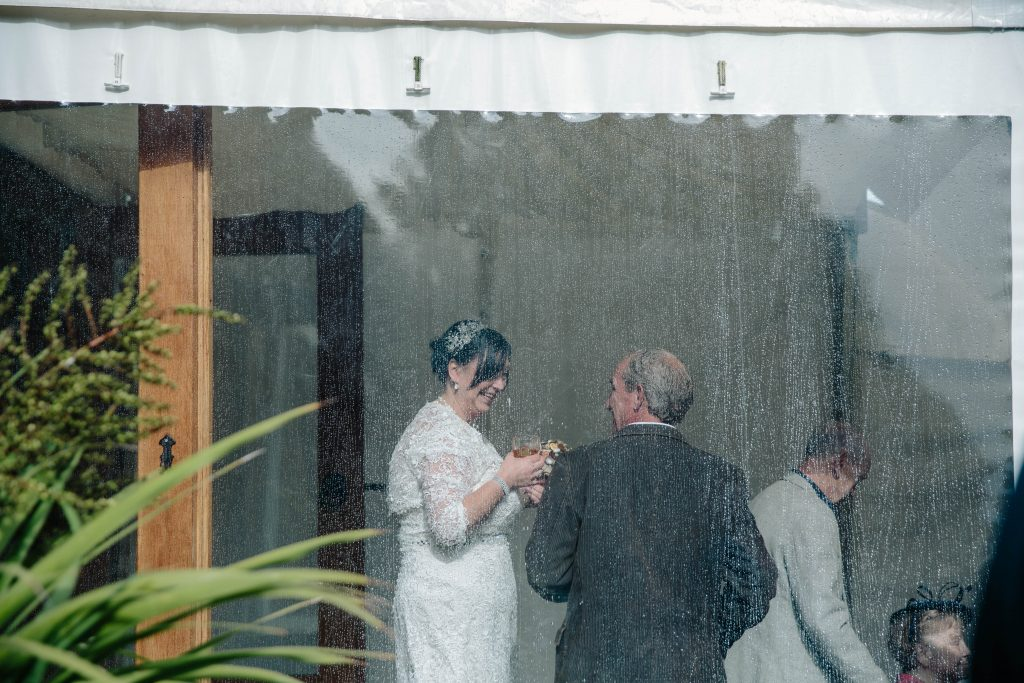 Bride chatting to guests, photographed through the window