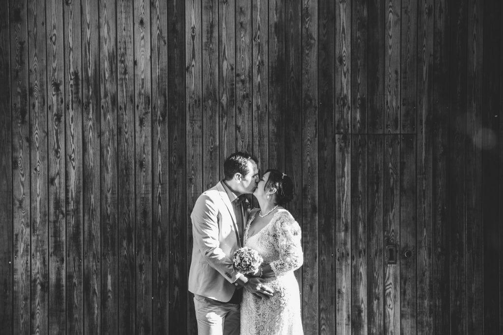 Bride & Groom kissing outside barn doors