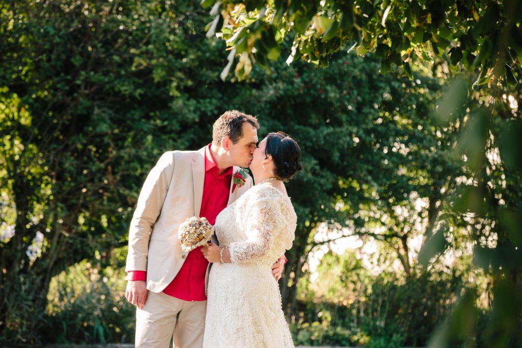 Bride & Groom kissing outside, at Dovecote Barn