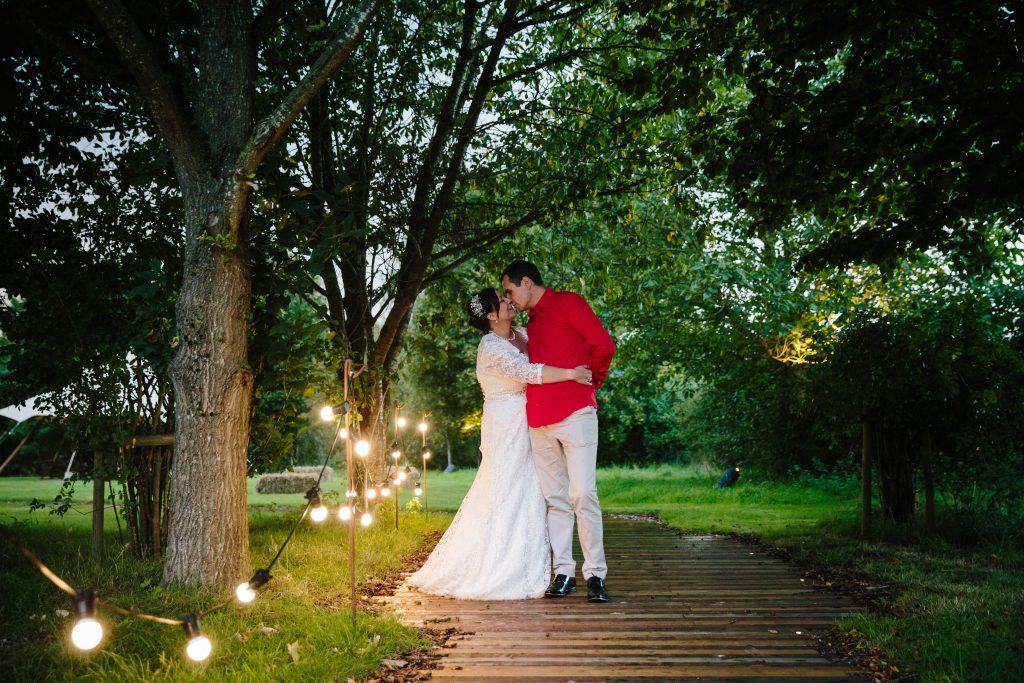 Bride & Groom kissing outside by fairy lights at Dovecote Barn