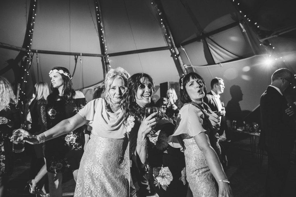 Guests posing on dance floor, tipi wedding