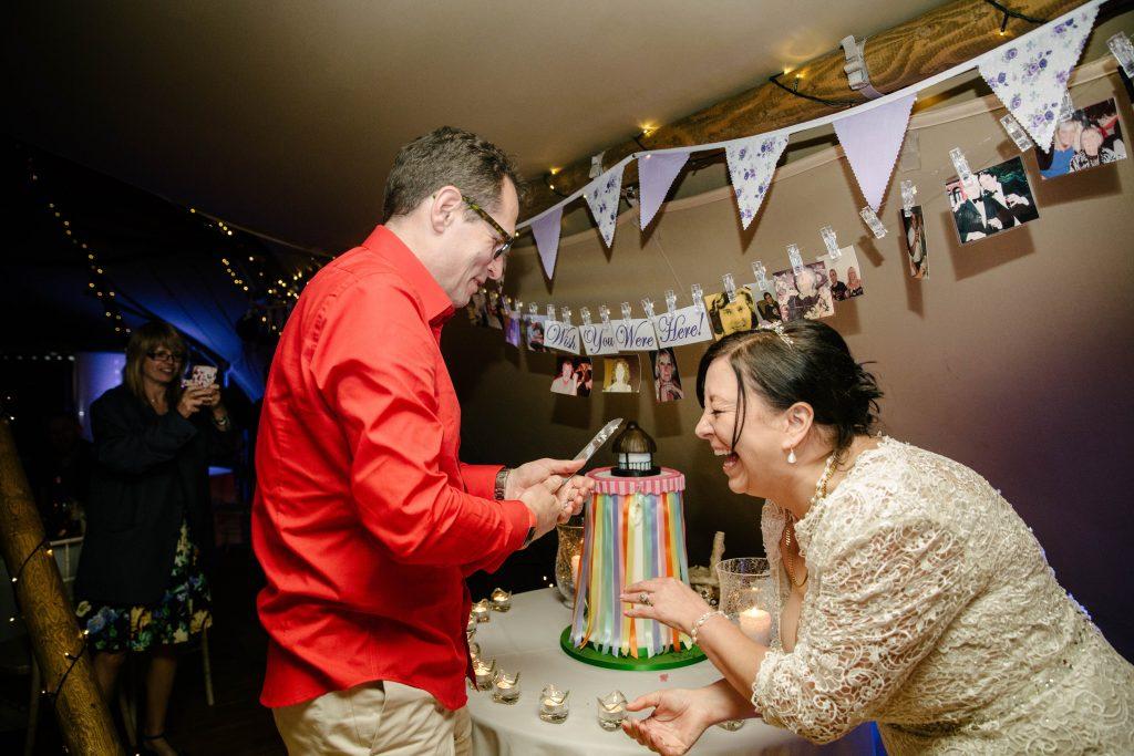 Bride & Groom laughing, cutting the wedding cake
