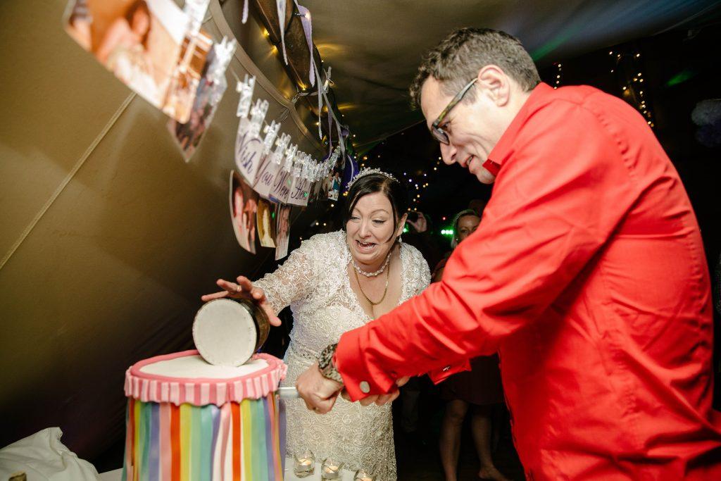 Bride & Groom laughing as cake falling at wedding