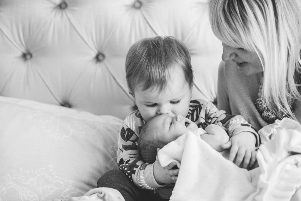 Big brother cuddling and kissing his newborn baby sister