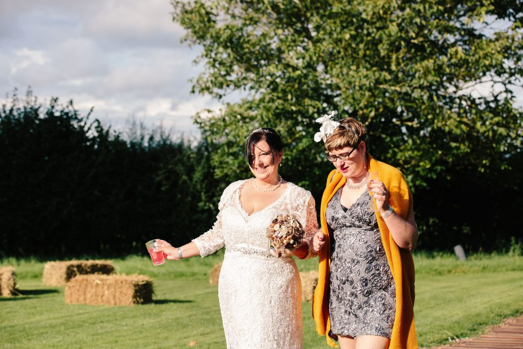 Bride walking with guest at wedding