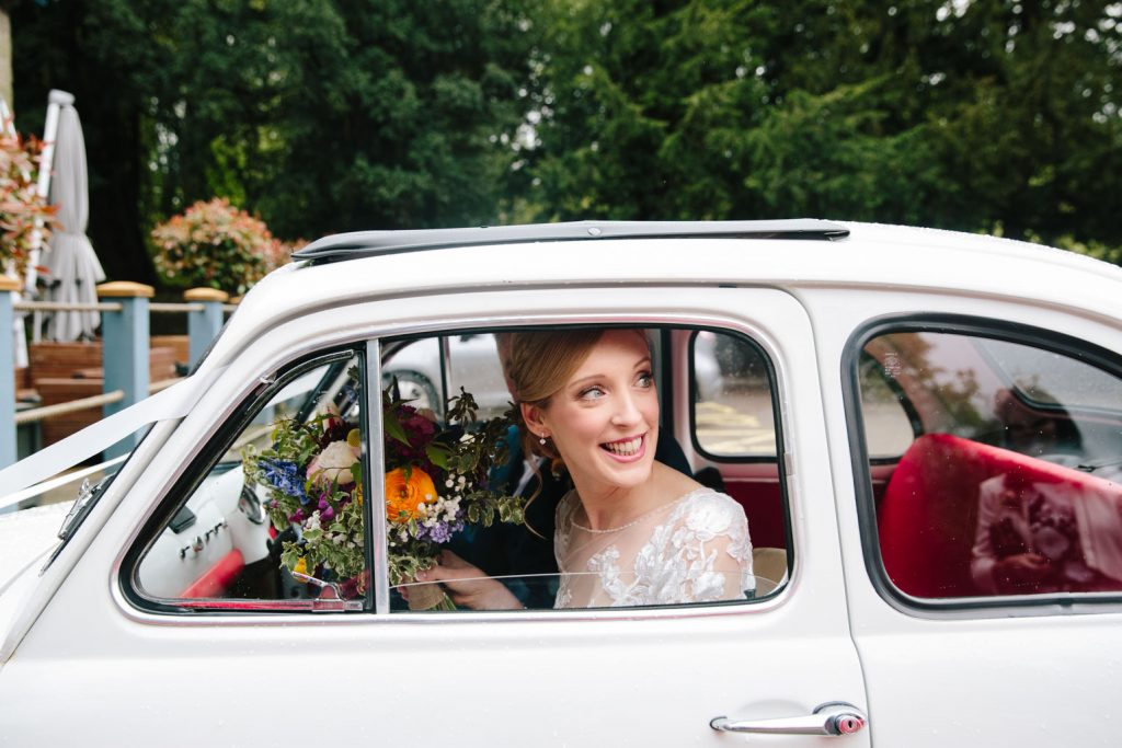 Bride arriving at her wedding at the Saxon Mill in her Fiat 500
