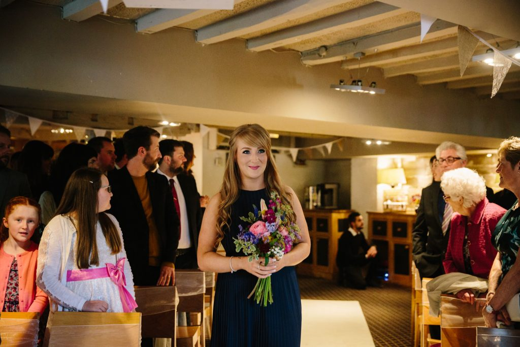 Bridesmaid walking up the aisle at the saxon Mill in Warwickshire