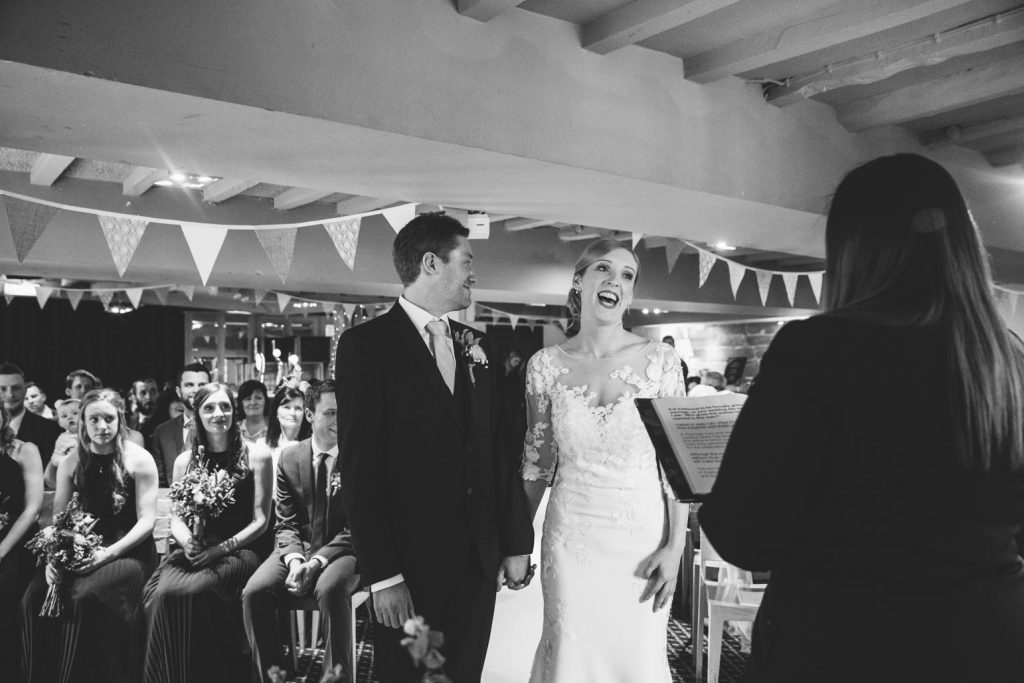 Bride & Groom laughing during wedding ceremony at the Saxon Mill