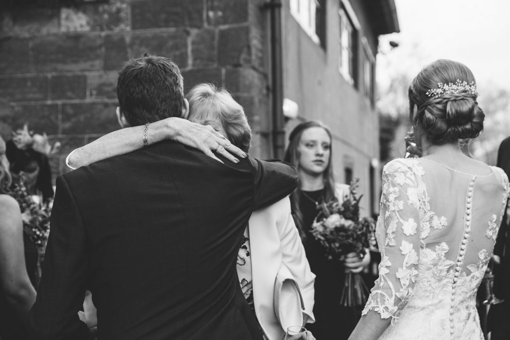 Groom hugging mother at wedding, Saxon Mill